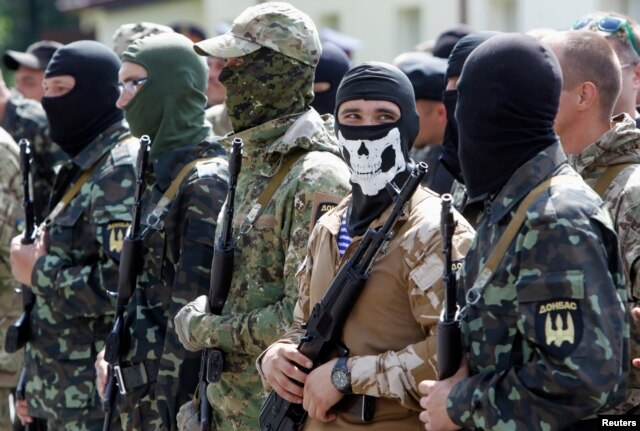 "FILE - Members of the ""Donbas Battalion"" take part in a swearing in ceremony near Kyiv, June 23, 2014."