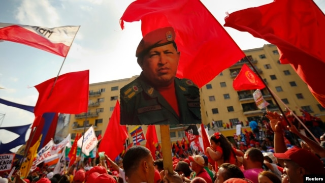 FILE - A supporter of Venezuela's President Nicolas Maduro holds up a picture of late president Hugo Chavez during a May Day demonstration in Caracas, May 1, 2014.
