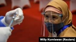 Seorang perempuan bersiap menerima suntikan vaksin Sinovac selama program vaksinasi massal di Bursa Efek Indonesia di Jakarta. (Foto: REUTERS/Willy Kur