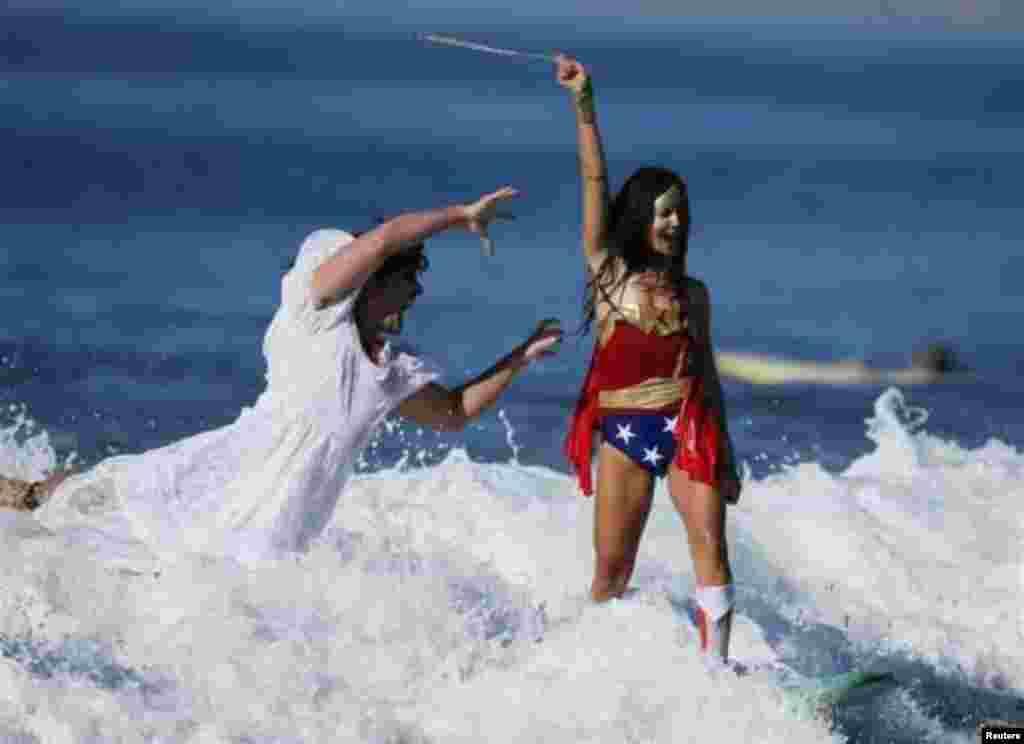 دنیز ویلینگ و کوین شوایمر در نقش شخصیت کارتونی «زن شگفتانگیز» و «عروس مرده» در مسابقات موج سواری هالووین – سانتامونیکا، کالیفرنیا، ۴ آبان ۱۳۹۳