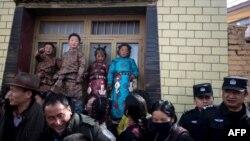 2018年3月1日,多名西藏兒童穿上傳統服裝慶祝西藏新年,旁邊有武警監視。