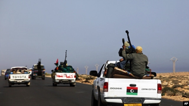 A convoy of rebels travel in the direction of Libyan leader Moammar Gadhafi's hometown of Sirte city near Bin Jawad, March 28, 2011