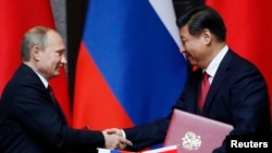 Tổng thống Nga Vladimir Putin (trái) và Chủ tịch Trung Quốc Tập Cận Bình bắt tay sau khi ký kết một thỏa thuận 20/5/14