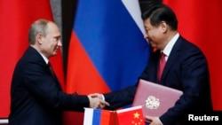 Presiden Rusia Vladimir Putin (kiri) dan Presiden China Xi Jinping berjabat tangan seusai penandatangan perjanjian bilateral di Shanghai (20/5).