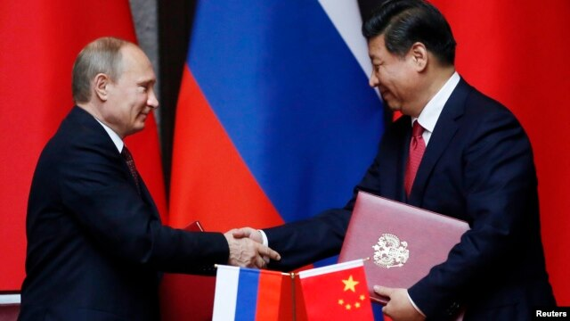 Russia's President Vladimir Putin (L) and China's President Xi Jinping shake hands after signing an agreement during a bilateral meeting at the Xijiao State Guesthouse ahead of the fourth Conference on Interaction and Confidence Building Measures in Asia
