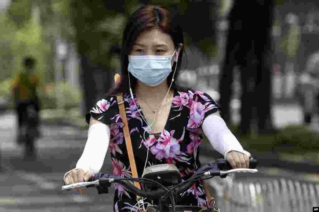 တရုတ္ႏိုင္ငံ Beijing ၿမိဳ႕က Electric စက္ဘီစီးသြားသူ အမ်ိဳးသမီးတဦး။ (ဇြန္ ၁၉၊ ၂၀၂၀)