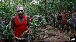 En avant-plan, Njikali conduit une cérémonie marquant le passage d'un camp de chasse à un autre sur les terrains de chasse traditionnels de sa famille dans la Réserve de faune à okapis près de la ville d'Epulu, RD Congo.