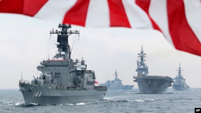 Japan Maritime Self-Defense Force (JMSDF) escort ship Kurama, left, leads other vessels during a fleet review in waters off Sagami, south of Tokyo, October 14, 2012.