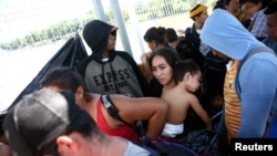 Central American migrants line up at a bridge that connects Guatemala to Mexico.