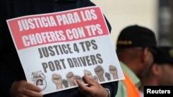 """Một người biểu tình cầm một tấm biển viết """"Công lý cho những người lái xe ở cảng được bảo vệ tạm thời (TPS)."""""""
