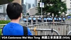 香港年青抗爭者6-12警民衝突前隔著鐵馬觀看特首辦入口的警方防線 (攝影:美國之音湯惠芸)