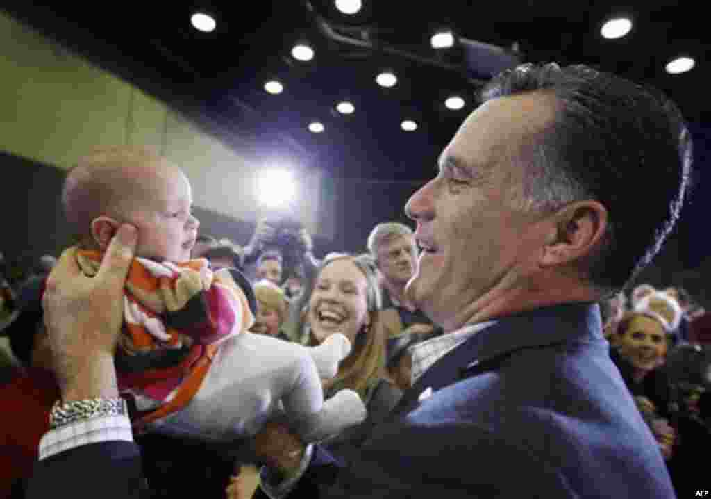 Republican presidential candidate, former Massachusetts Gov. Mitt Romney, picks up nine-week-old Laura Ensley from Augusta, Ga., as her mother, Mary Ensley watches at center, as he campaigns at the University of South Carolina Aiken, in Aiken, S.C., Frida