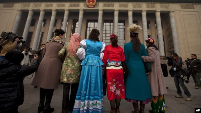 Uighur ethnic minority delegates in their traditional dresses pose for photos as they walk towards the Great Hall of the People for the opening session of the annual National People's Congress in Beijing, China, March 5, 2012.
