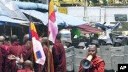 身穿蕃红色袈裟的缅甸僧侣与军警对峙