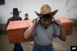FILE - An Ixil Mayan carries the remains of a civil war victim to a memorial for a mass burial in Santa Avelina, Guatemala, Nov. 30, 2017.
