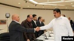 Presiden Venezuela Nicolas Maduro (kanan) berjabat tangan dengan sekjen koalisi Persatuan Demokrat (MUD), Jesus Torrealba (kiri) di Caracas, Venezuela, 30 Oktober 2016 (Miraflores Palace/Handout via REUTERS).