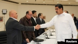 Venezuela's President Nicolas Maduro (R) shakes hands with Jesus Torrealba, secretary-general of Venezuela's coalition of opposition parties, during a political meeting between the government and the opposition, in Caracas, Venezuela, Oct. 30, 2016.