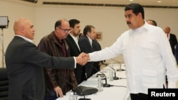 FILE - Venezuela's President Nicolas Maduro, right, shakes hands with Jesus Torrealba, left, secretary of Venezuela's coalition of opposition parties, during a political meeting between government and opposition, in Caracas, Venezuela, Oct. 30, 2016.