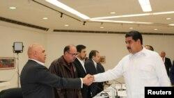 Prezidan venezuelyen an, Nicolàs Maduro, ki tap bay lanmen ak sekretè jeneral Kowalisyon Opozisyon Demokratik la (MUD), Jesùs Torrealba, pandan yon rankont ki dewoule Caracas nan jounen dimanch 30 oktòb 2016 la. (Foto: REUTERS/Palè nasyonal Miraflores).