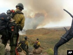 FILE - In this photo by firefighter Andrew Ashcraft, June 30, 2013, members of the Granite Mountain Hotshots watch a growing wildfire that later swept over and killed the crew of 19 firefighters near Yarnell, Arizona.