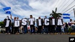 """En esta foto del 30 de mayo de 2018, los manifestantes antigubernamentales portan un cartel donde se lee """"Justicia"""", durante una marcha contra el presidente del gobierno de Nicaragua, Daniel Ortega, y su esposa, la vicepresidenta Rosario Murillo."""