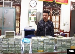 This handout taken by the Vietnam News Agency on February 25, 2018 and distributed on February 26 shows alleged drug smuggler and ringleader, Tran Van Bang, 31, standing before heroin bricks seized in the northern province of Cao Bang.