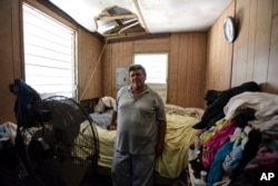FILE - Moises Valentin poses for a photo in his home damaged by Hurricane Maria, where the U.S. Army Corps of Engineers built him a temporary roof, in San Juan, Puerto Rico, Oct. 19, 2017.