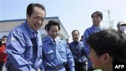 Thủ tướng Nhật Bản Naoto Kan bắt tay một cậu bé khi ông tới thăm thị trấn Ishinomaki bị sóng thần tàn phá hồi tháng trước