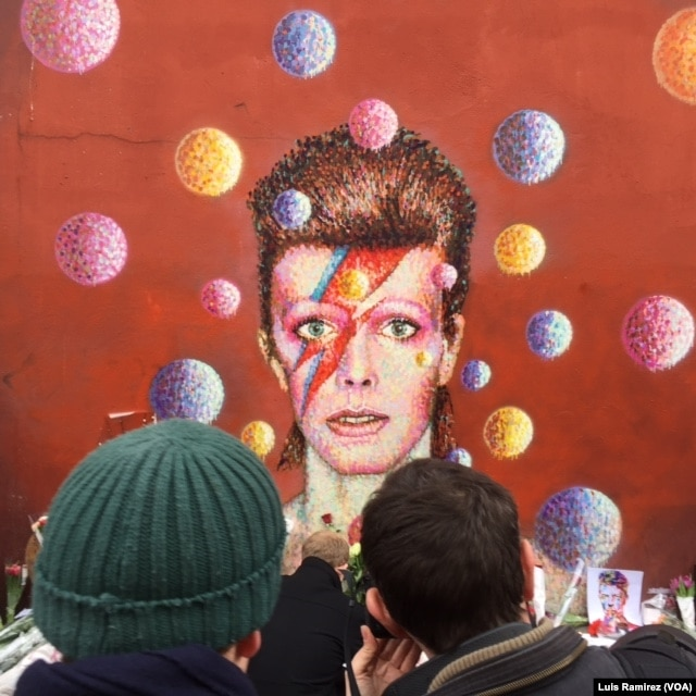 Fans gather Monday to mourn the death of David Bowie at a mural of the singer in his native London neighborhood of Brixton, Jan. 11, 2016.
