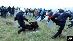 Polisi anti huru-hara bentrok dengan para migran yang berunjuk rasa di luar kamp pengungsi di desa Diavata, sebelah barat Thessaloniki, utara Yunani, 6 April 2019 (foto: AP Photo/Giannis Papanikos)