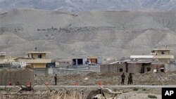 Afghan army forces stand guard as the view of the military base is seen in the background after suicide bomber has blew himself up at the entrance to the military base in eastern province of Laghman, east of Kabul, April 16, 2011