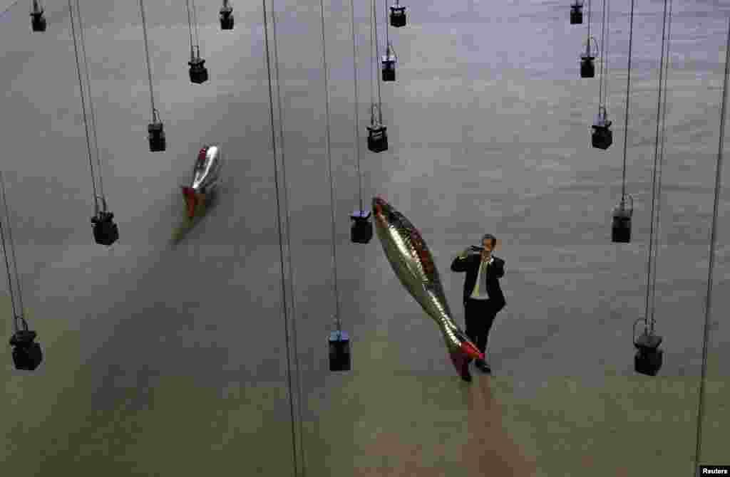 បុរសម្នាក់ថតរូបស្នាដៃសិល្បៈ «Anywhere» ដោយសិល្បករបារាំងលោក Philippe Parreno ក្នុងសាល Turbine Hall នៅឯមជ្ឈមណ្ឌល Tate Modern ក្រុងឡុងដ៍ ចក្រភពអង់គ្លេស។