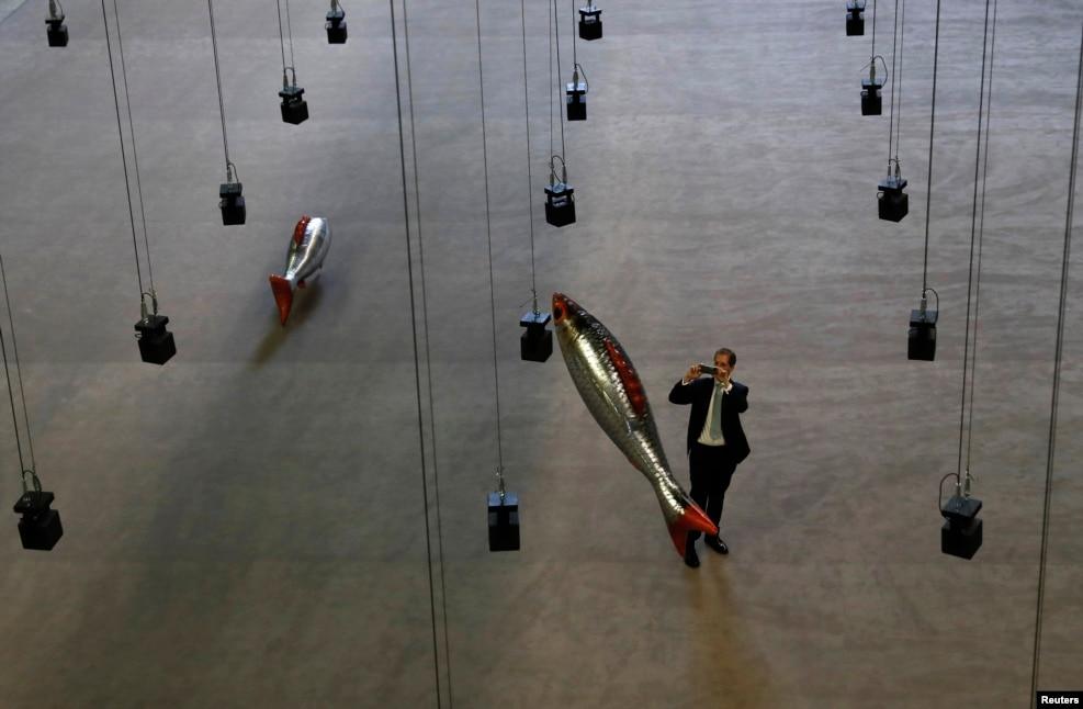 """Müsafir fransız artist Filipp Parrenonun """"Hər yerdə"""" adlı əl işinin fotosunu çəkir. London, Britaniya."""