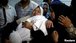 A relative mourns as she carries the body of 8-month-old Palestinian infant Laila al-Ghandour, who died after inhaling tear gas during a protest against the U.S. embassy move to Jerusalem, at the Israel-Gaza border, during her funeral in Gaza City, May 15, 2018.