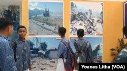 Sekelompok pelajar yang menyaksikan foto-foto dokumentasi dampak bencana alam yang dipajang dalam kegiatan pameran khusus sejarah alam dan kebencanaan oleh Museum Sulawesi Tengah, 8 Oktober 2019. (Foto: VOA/Yoanes Litha)