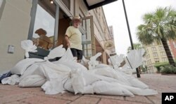 Lynn Dixon places sandbags outside their home decor store in Galveston, Texas as Hurricane Harvey intensifies in the Gulf of Mexico, Aug. 25, 2017.
