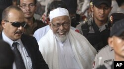 Radical cleric Abu Bakar Bashir, center, leaves the court after the judges delivered his sentence during his trial at a district court In Jakarta, Indonesia, June 16, 2011