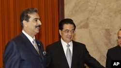 Pakistani Prime Minister Yousuf Raza Gilani, left, is shown the way by Chinese President Hu Jintao during a meeting at the Great Hall of the People in Beijing, May 20, 2011