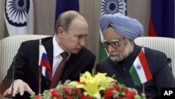 Russian President Vladimir Putin, left, talks with Indian Prime Minister Manmohan Singh at a press conference after signing weapons deals worth billions in New Delhi, India, Monday, Dec. 24, 2012.