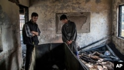 FILE - Kashmiri Muslim student Hilal Ahmed Hajam, left, and Nasir Ahmed Mir inspects the damage of a partially burned government high school in Goripora, outskirts of Srinagar, India controlled Kashmir, Nov. 1, 2016.