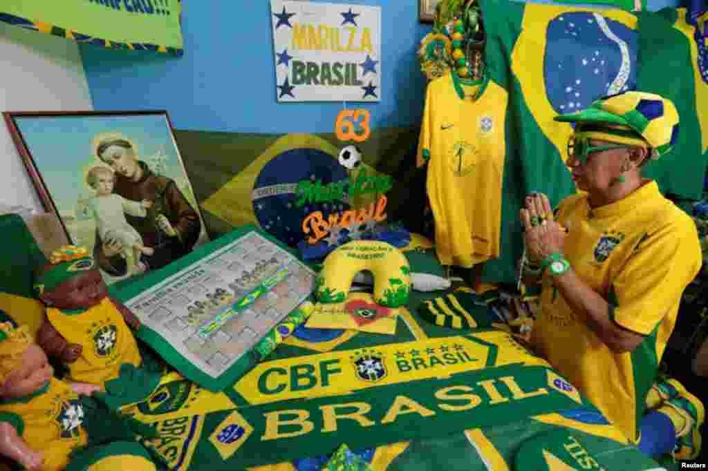 A senhora de 63 anos, Marilza, reza no seu santuário, todo decorado com os elementos da selecção brasileira, na sua casa em Brasília, Maio 27, 2014. REUTERS/Joedson Alves
