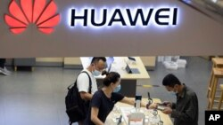 Visitors wearing masks to curb the spread of the coronavirus look at the latest products at a Huawei store in Beijing on Wednesday, July 15, 2020. (AP Photo/Ng Han Guan)