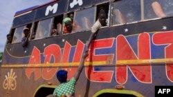 ນາງ Ntahombaye Melania ມືໄປຈັບມືຜົວຂອງນາງ ທີ່ໄດ້ຫລົບໜີຈາກ Burundi ໃນປີ 2015 ໃນຂະນະທີ່ລາວຂີ່ລົດເມມາເຖິງຊາຍແດນ Gisuru ຢູ່ແຂວງ Ruyigi ຂອງ Burundi, ໃນວັນທີ 3 ຕຸລາ, 2019