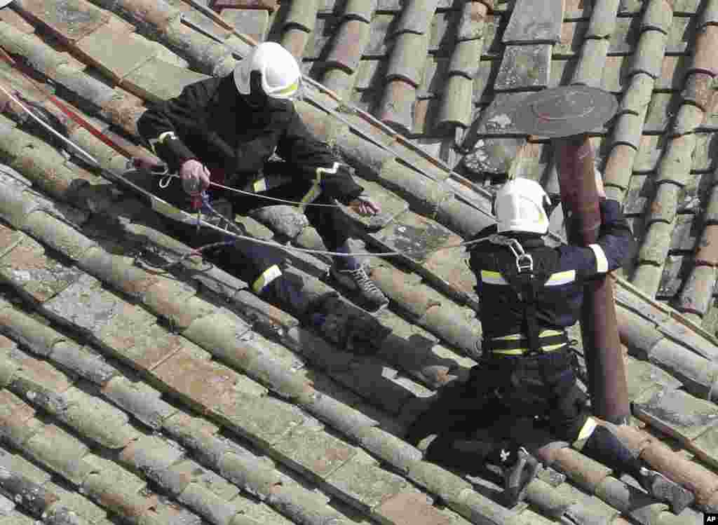 Firefighters place the chimney on the roof of the Sistine Chapel, where cardinals will gather to elect the new pope, at the Vatican. The conclave date was set during a vote by the College of Cardinals, who have been meeting all week to discuss the church's problems and priorities, and the qualities the successor to Pope Benedict XVI must possess.