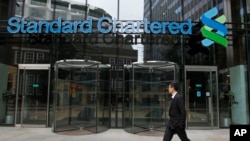FILE - In this Aug 7, 2012, file photo a man walks by Standard Chartered bank in London. British financial services giant Standard Chartered Bank will pay $1.1 billion in fines to settle allegations by U.S. and British authorities that it attempted to eva