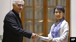 Burma opposition leader Aung San Suu Kyi, and Indian Foreign Minister Salman Khurshid pose for the media before a meeting in New Delhi, India, November 15, 2012.