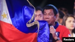 Philippine president Rodrigo 'Digong' Duterte holds a Philippine flag while addressing his supporters.