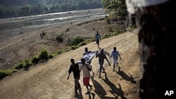 Michelet Compere, 14, suffering from cholera, is carried on a stretcher by relatives during their four-hour journey from a remote village in Pond Chevalier to the hospital in Grande Riu Du Nord village, Haiti, Nov 29, 2010