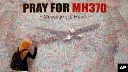 """Žena piše poruku za putnike na letu broj 370 """"Malezija Erlajnsa"""" na zidu jednog tržnog centra u Kuala Lumpuru"""