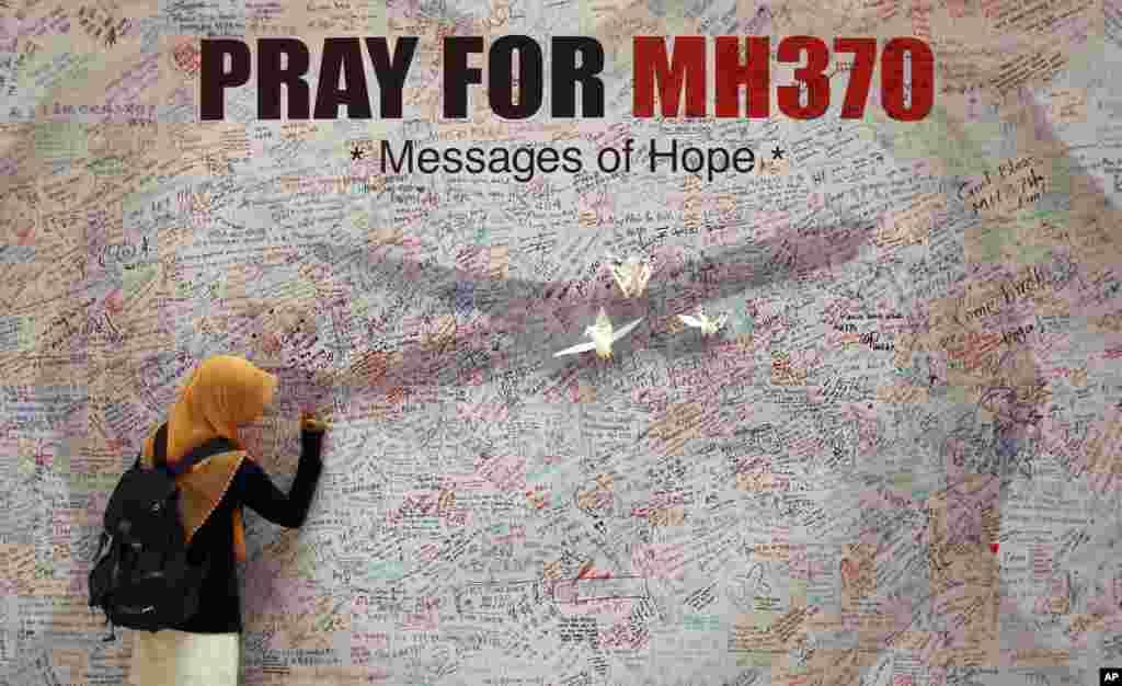 Một phụ nữ viết lời cầu nguyện cho những hành khách trên chiếc máy bay mất tích của hãng Malaysia Airlines tại một thương xá ở Kuala Lumpur, Malaysia. Các nhà điều tra kết luận có một hay nhiều người có kinh nhiệm lái máy bay đã cướp chiếc máy bay, tắt các máy móc liên lạc và lái đi hướng khác.